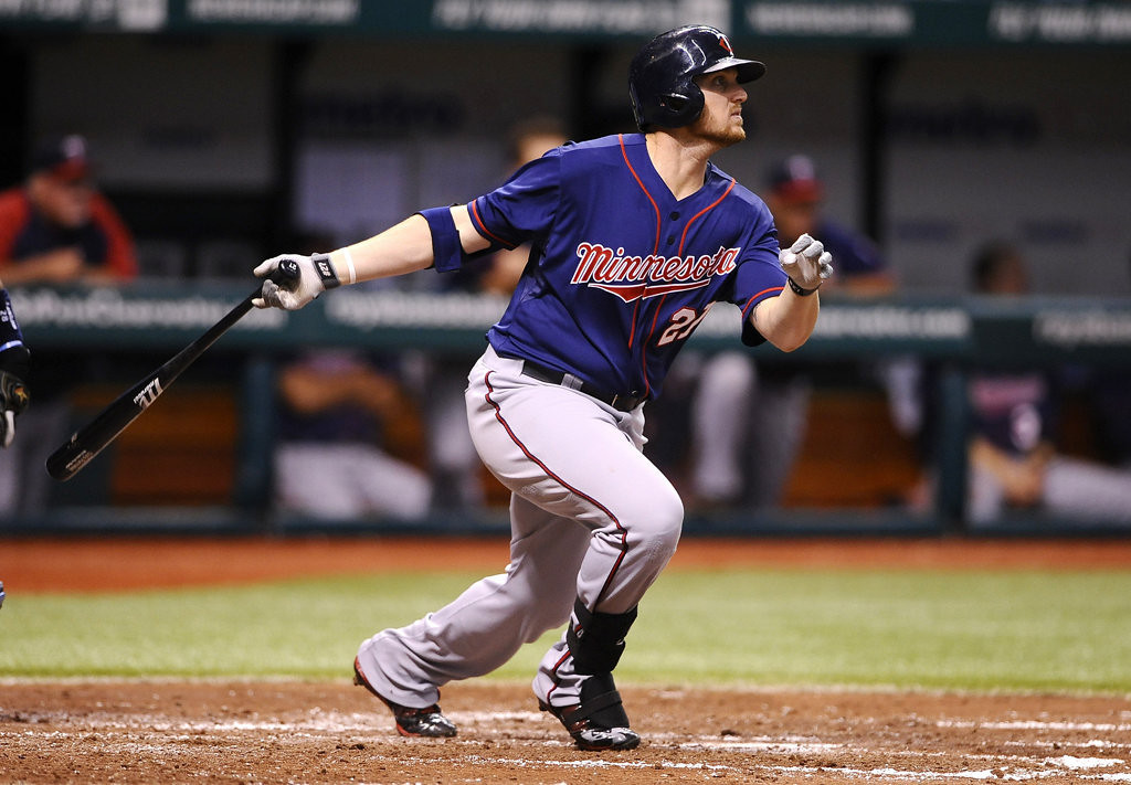 . Minnesota Twins\' Chris Parmelee follows through as he hits a sacrifice fly to right field to score Trevor Plouffe during the fourth inning. (AP Photo/Brian Blanco)