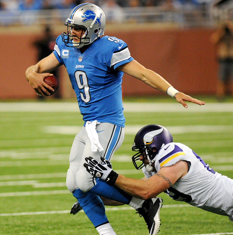 . Lions quarterback Matthew Stafford is in the grasp of Vikings defensive end Jared Allen as he runs the ball in the first quarter.  (Pioneer Press: Chris Polydoroff)
