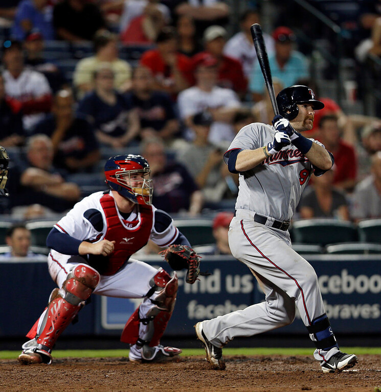 . Minnesota Twins\' Ryan Doumit follows through with an RBI base hit as Atlanta Braves catcher Brian McCann watches in the eighth inning. (AP Photo/John Bazemore)