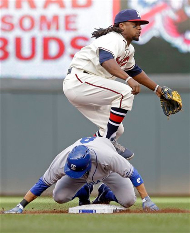 . Milwaukee Brewers second baseman Rickie Weeks jumps clear of Minnesota Twins\' Jamey Carroll after the force at second and completes the double play hit into by Twins\' Brian Dozier in the first inning of a baseball game Thursday, May 30, 2013 in Minneapolis. (AP Photo/Jim Mone)