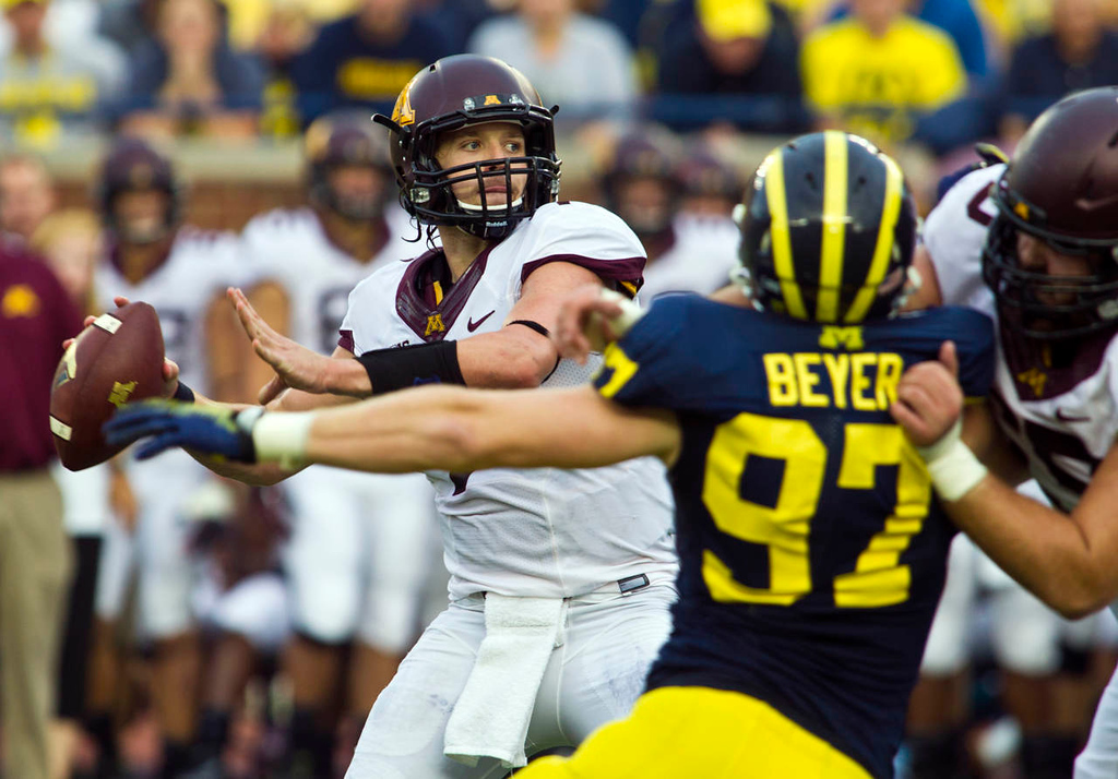 . Minnesota quarterback Mitch Leidner looks to throw a pass under pressure from Michigan linebacker Brennen Beyer in the fourth quarter. (AP Photo/Tony Ding)