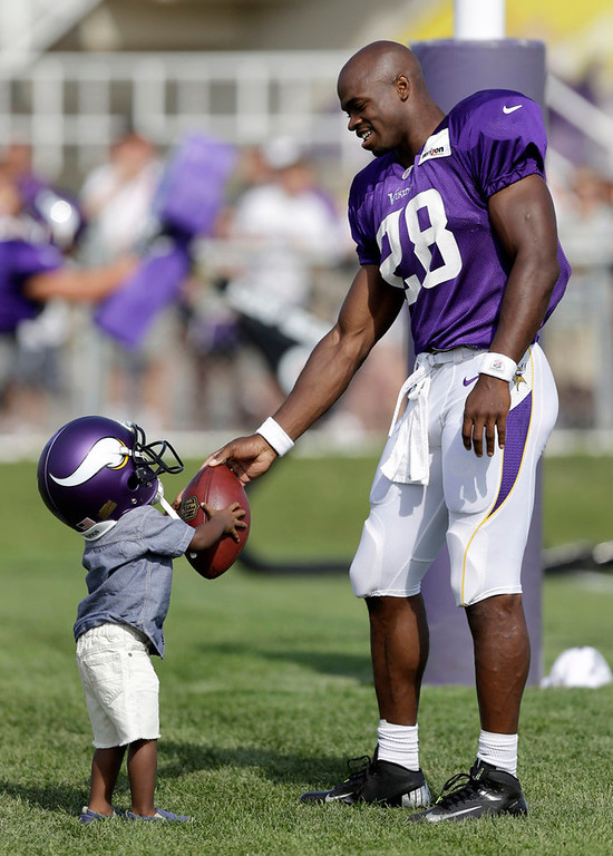 . Vikings running back Adrian Peterson makes the hand off to his son Adrian Jr. at the end of practice. (AP Photo/Charlie Neibergall)