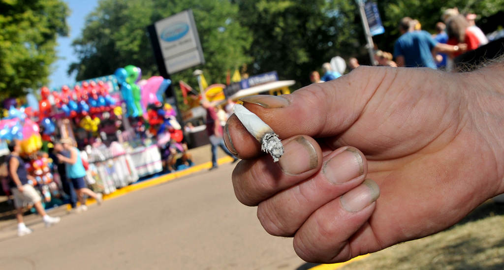 . A fairgoer enjoys his smoke at a designated area near the Dairy Building at the Minnesota State Fair on Friday, Aug. 23, 2013. Smoking has been limited to 18 stations set up around the Minnesota Fairgrounds. (Pioneer Press: John Doman)