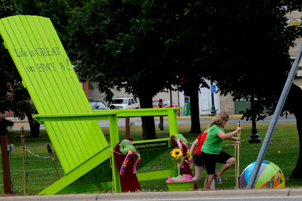 . After standing by a big chair in Chisago City and posing for a picture, two girls walk away Friday July 26, 2013. (Pioneer Press: Jean Pieri)