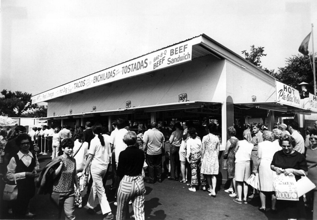 . 1970 Minnesota State Fair. Mexican Village - Long, steady lines of Mexican food enthusiasts were in evidence at the large cafe-style stand. Just to the left is a roomy patio dining area with umbrella tables for customer comfort. Photo courtesy of the Minnesota State Fair.