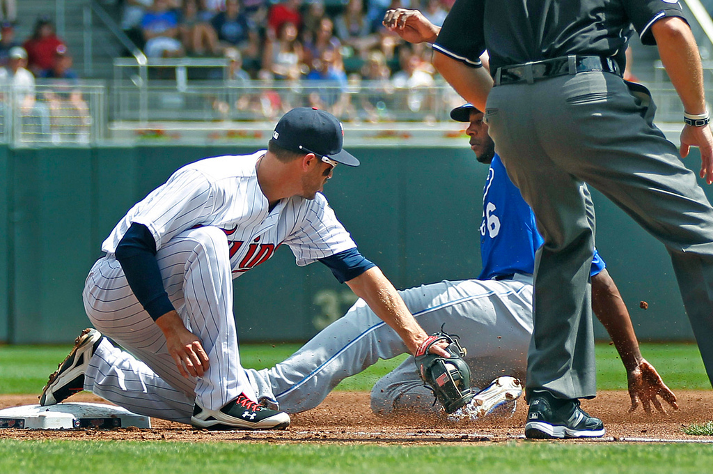 . Kansas City\'s Lorenzo Cain advances safely into third on a sacrifice fly as Twins third baseman Trevor Plouffe makes a late tag in the second inning.  (AP Photo/Andy Clayton-King)