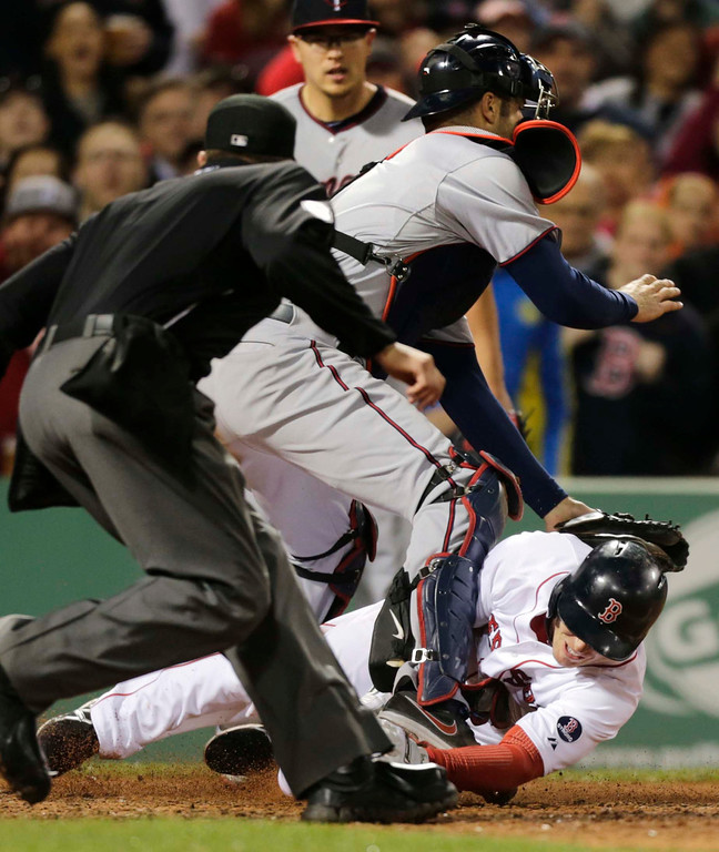 . Boston Red Sox\'s Stephen Drew, bottom, tries to beat a tag by Minnesota Twins catcher Joe Mauer on a double by Jacoby Ellsbury during the fifth inning. Drew was out on the play. At left is home plate umpire Cory Blaser. (AP Photo/Charles Krupa)