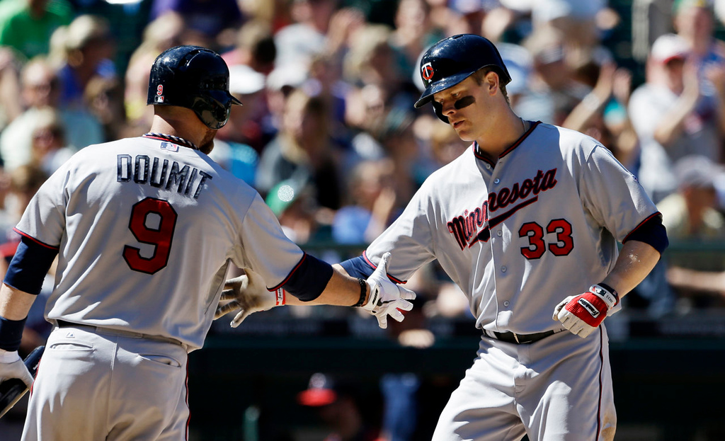 . Minnesota Twins\' Justin Morneau (33) is greeted at home by Ryan Doumit on his home run against the Seattle Mariners in the seventh inning. (AP Photo/Elaine Thompson)