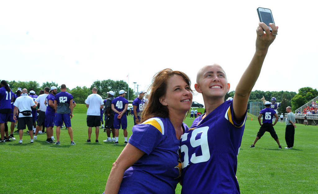 ". Charlotte Fournier, left, and her daughter, Taylor Fournier, of Andover shoot ""selfies\"" on the Vikings practice field as the team works out behind them.   (Pioneer Press: John Doman)"
