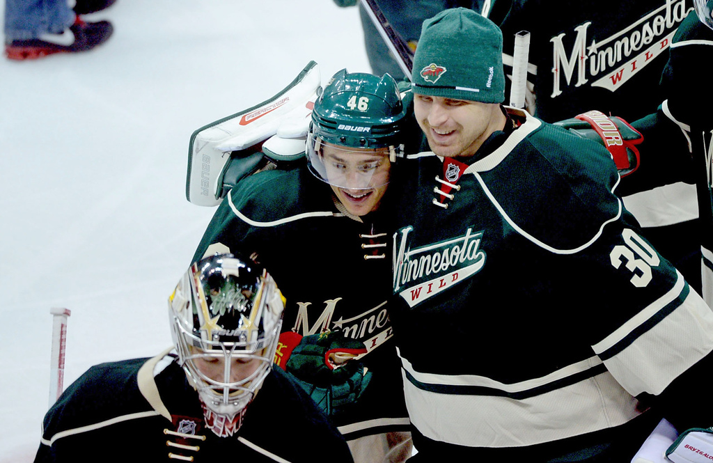 . Minnesota goaltender Darcy Kuemper, bottom, leaves the ice as fellow goalie Ilya Bryzgalov, top right, hugs teammate Jared Spurgeon after Minnesota\'s 1-0 win over the Colorado Avalanche. (Pioneer Press: Sherri LaRose-Chiglo)