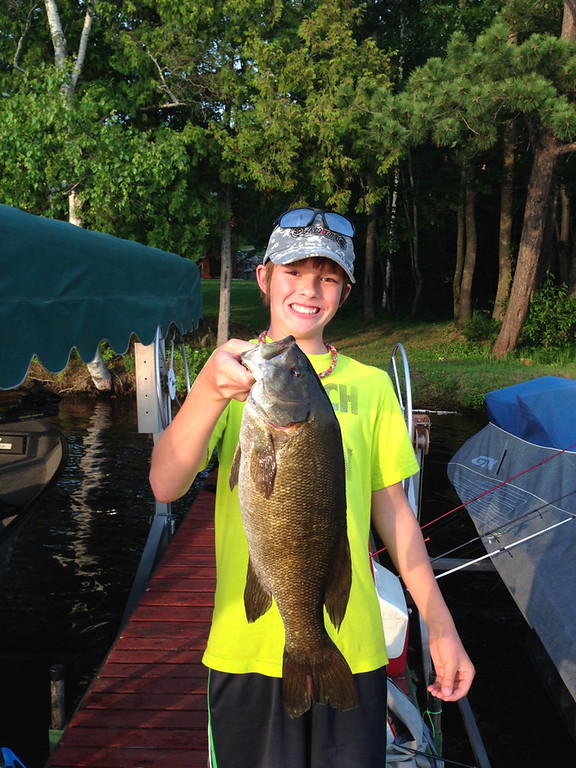 """. Ethan Vanden Busch, 12, of Lakeville, hoists a 20-inch smallmouth bass caught with a bobber and shiner off the dock on Big Thunder Lake in Remer July 19.  Here\'s the story, according to Angela Vanden Busch: \""""Ethan\'s uncle, Greg Seiffert, had a big fish on his line first, but it broke the line, taking the hook with it.  Soon after that, Ethan hooked his fish and sure enough, there was a second hook in its mouth.\"""" (Courtesy Angela Vanden Busch)"""
