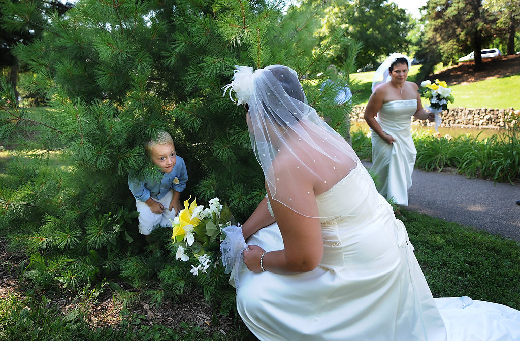 . Rochelle tries to coax the ring bearer Aiden Johnson, 3, of Panama City, Fla., out from his hiding spot so he can be in wedding pictures before their wedding. Johnson is the nephew of Shirley Otto, right. (Pioneer Press: Jean Pieri)
