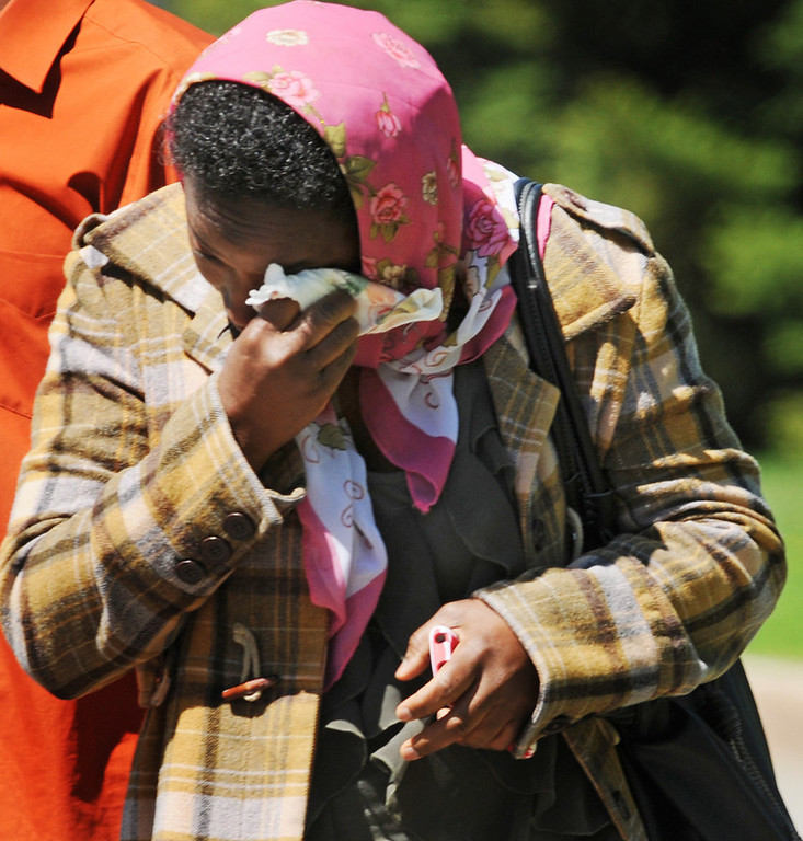 . A relative of 10-year-old Zack Mohamed Fofana walks down Annapolis Street to her car in St. Paul on Thursday after the boy\'s body was found and taken from a mass of rock and soil that slid down a Lilydale Regional Park bluff a day earlier. (Pioneer Press: Jean Pieri)