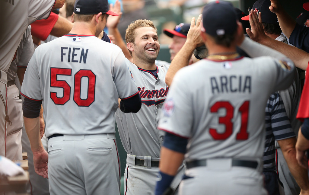 . Minnesota Twins\' Brian Dozier, center, is congratulated after his three-run home run by teammates Casey Fein, left, and Oswaldo Arcia against the Colorado Rockies in the ninth inning. (AP Photo/David Zalubowski)
