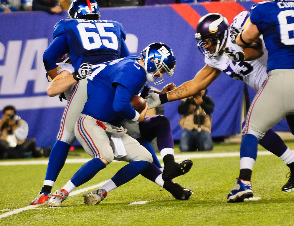 . Vikings defensive end Jared Allen refuses to let go of Giants quarterback Eli Manning for a sack late in the second quarter. (Pioneer Press: Ben Garvin)