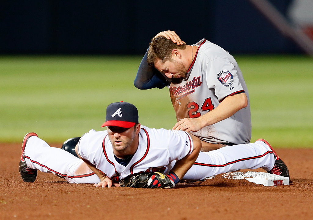 . Trevor Plouffe #24 of the Minnesota Twins reacts after colliding with Dan Uggla #26 of the Atlanta Braves at second base in the 10th inning at Turner Field on May 21, 2013 in Atlanta, Georgia.  (Photo by Kevin C. Cox/Getty Images)