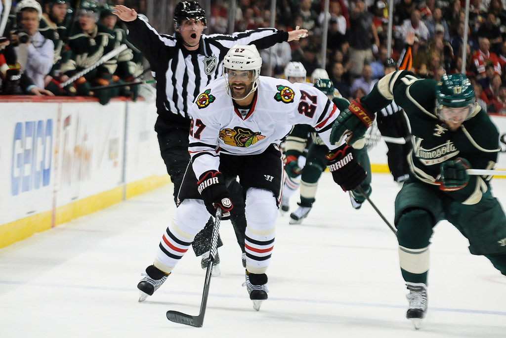 . Minnesota left wing Mike Rupp, left, and Chicago defenseman Sheldon Brookbank skate during the first period.  (Pioneer Press: Ben Garvin)