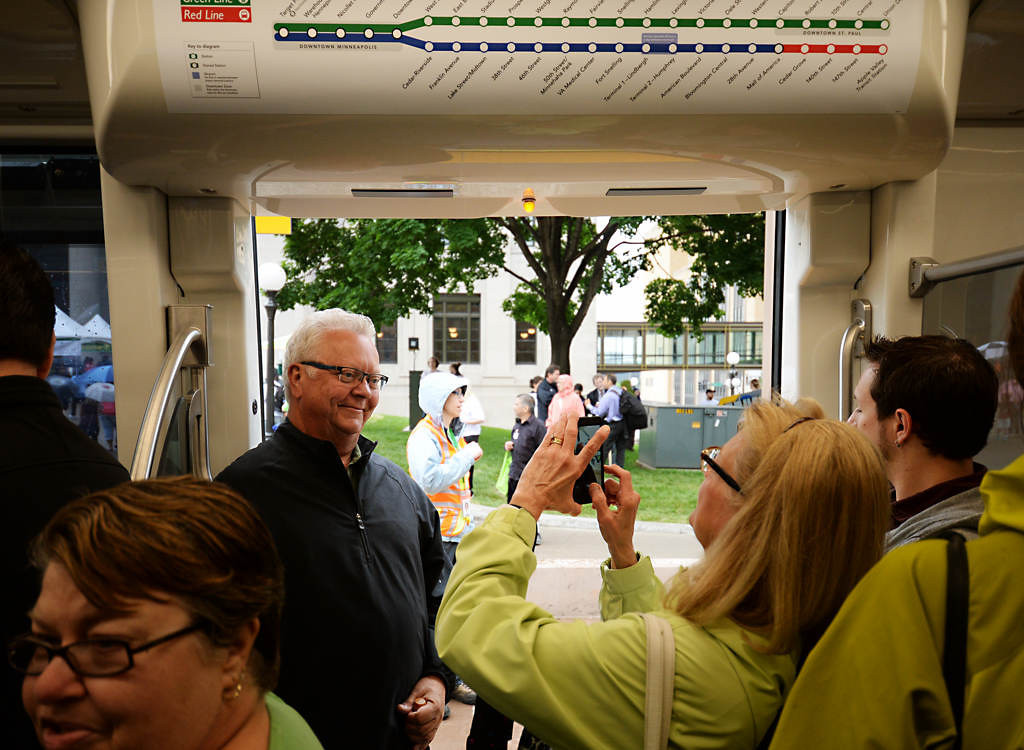 """. Tom Jensen has his photo taken by his wife Mary Jo Jensen, both from Eagan, as they wait for the train to close it doors during the Metro Transit Green Line Grand Opening in St. Paul.. \""""We wanted to be part of the fun,\"""" said Tom Jensen. (Pioneer Press: John Autey)"""