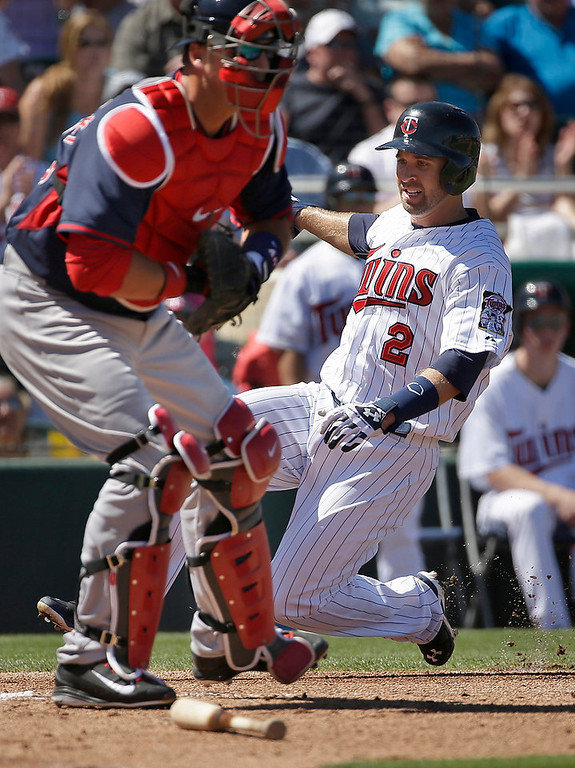 . Minnesota Twins\' Brian Dozierin, right, scores on an RBI single by Joe Mauer as Boston Red Sox catcher A.J. Pierzynski, left, tries to make the play in the first inning of an exhibition baseball game, Saturday, March 1, 2014, in Fort Myers, Fla. (AP Photo/Steven Senne)