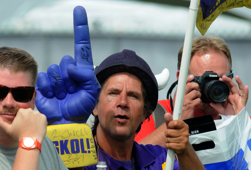 . Vikings fan Rich Childs of Elysian, Minn., center, brandishes his purple foam finger during the team\'s morning workout, keeping it out of the way of his fellow fan at right..   (Pioneer Press: John Doman)