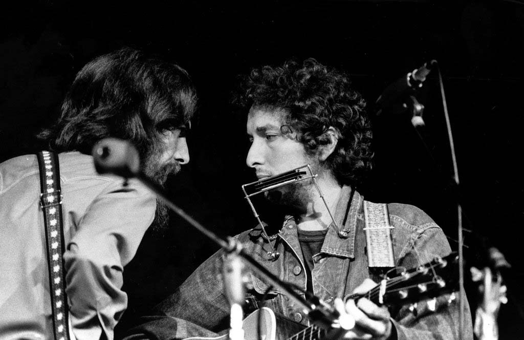 . George Harrison, left, and Bob Dylan look at each other as they perform during a benefit concert at Madison Square Garden in New York City, Aug. 1, 1971.  The proceeds from the concert will aid refugees of East Pakistan.  (AP Photo)