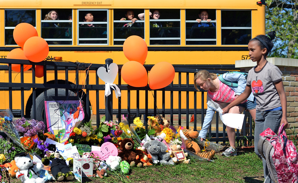 . At the end of the school day, a girl, right, places flowers by a makeshift memorial in front of Peter Hobart Elementary School in St. Louis Park on Thursday, in memory of the two students who died in a landslide while on a field trip to Lilydale Regional Park in St. Paul on Wednesday. (Pioneer Press: Chris Polydoroff)