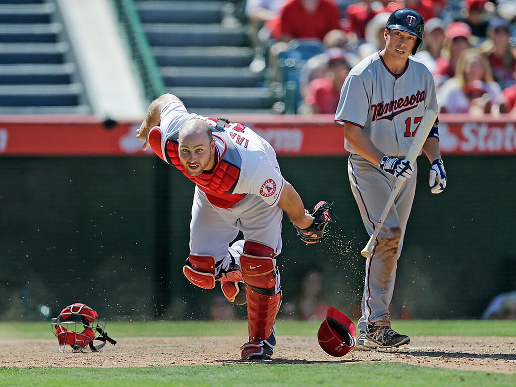 . Angels catcher Chris Iannetta, left, goes after a foul ball bunt attempt by Minnesota\'s Doug Bernier, right, during the ninth inning. (AP Photo/Jae C. Hong)