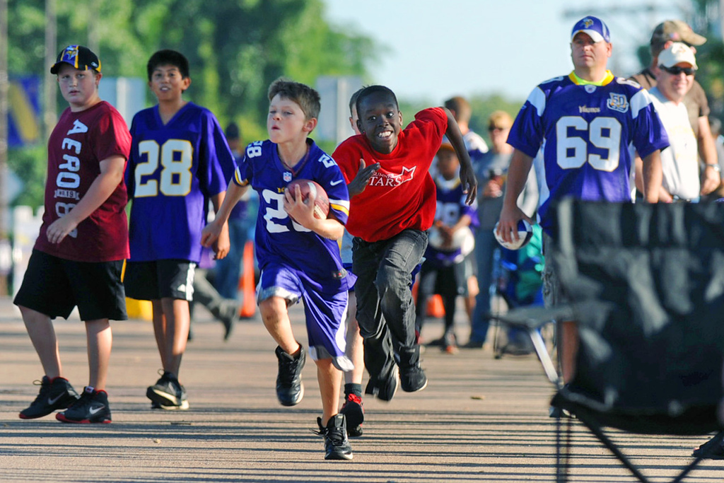 . Young Vikings fans play a game of touch football while several hundred people waited in line to get into the last day of training camp.  (Pioneer Press: Chris Polydoroff)