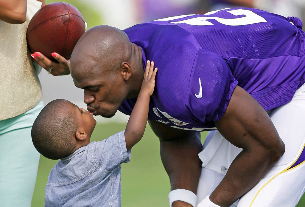 . Vikings running back Adrian Peterson gets a motivational smooch from his son Adrian Jr. during Day 3 of the team\'s 2013 training camp in Mankato on Monday, July 29, 2013. (AP Photo/Charlie Neibergall)