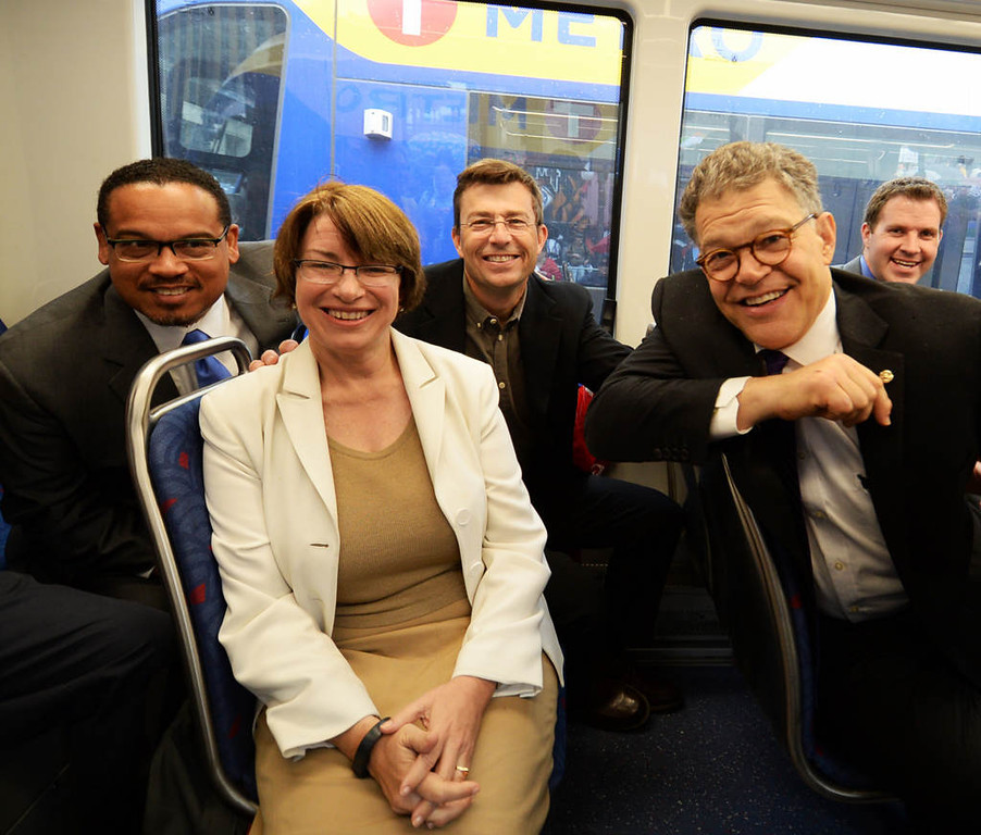 . Minnesota Congressman Keith Ellison, left, poses for a photo with U.S. Senators Amy Klobuchar and Al Franken and Hennepin County Commissioner Mike Opat, back middle , pose for a photo aboard the inaugural train during the Metro Transit Green Line Grand Opening in St. Paul. (Pioneer Press: John Autey)