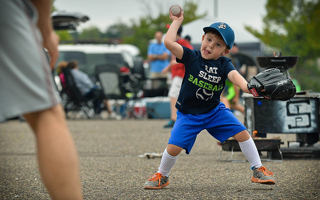". Season ticket holder Riley Klava, 4, of Roseville, fields a ball for this father Jon, left, while tailgating before the game. ""I\'ve been taking him here before he can walk,\"" said Jon. (Pioneer Press: Ben Garvin)"