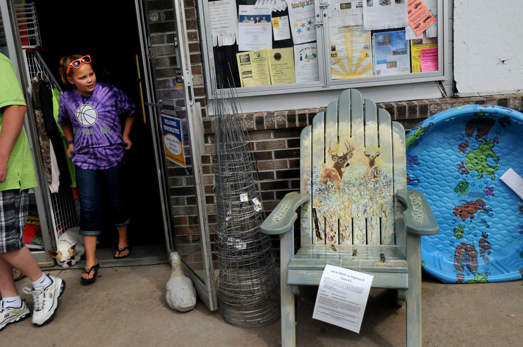 """. Jenna Whitmore, 11, River Falls, walks out of a Chisago True Hardware store Friday July 26, 2013. The chair by the store is titled \""""A Moment to Remember\"""" by Steve Levey and is part of the Highway 8 Chairs project in Chisago County. (Pioneer Press: Jean Pieri)"""