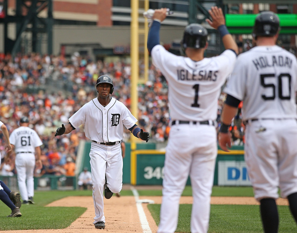 . Detroit\'s Austin Jackson, left, spots teammates Jose Iglesias, center and Bryan Holaday as he trots home following his three-run home run to left field off Twins reliever Josh Roenicke in the sixth inning. Both Iglesias and Holaday scored on the play.  (Photo by Leon Halip/Getty Images)