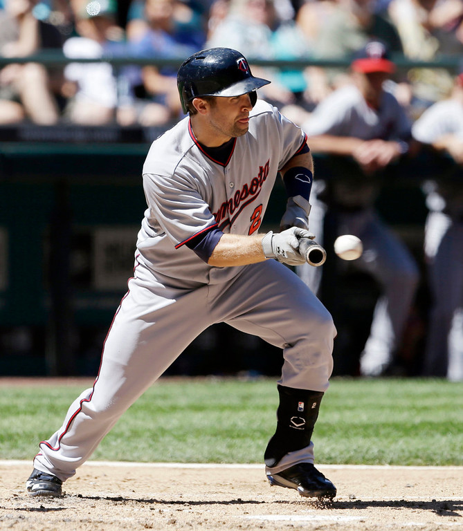 . Minnesota Twins\' Brian Dozier bunts against the Seattle Mariners in the third inning. AP Photo/Elaine Thompson)