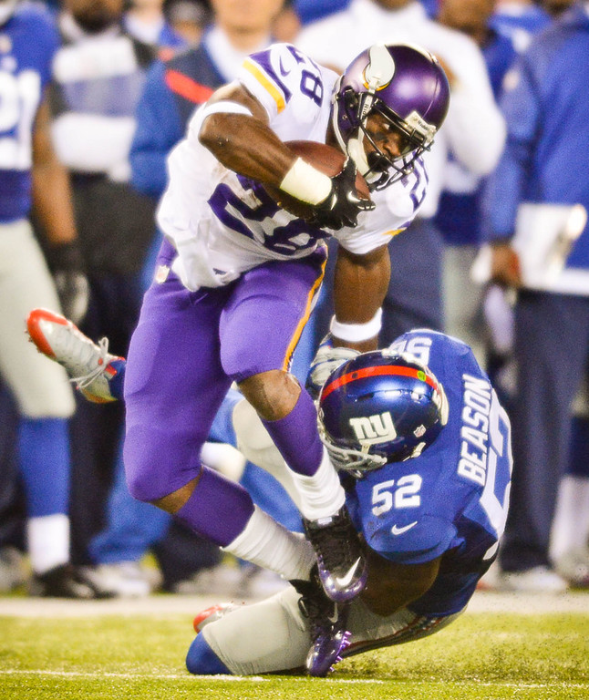 . Vikings running back Adrian Peterson is pulled down by Giants middle linebacker Jon Beason in the third quarter. Peterson carried the ball 13 times, for only 28 yards in the game.  (Pioneer Press: Ben Garvin)