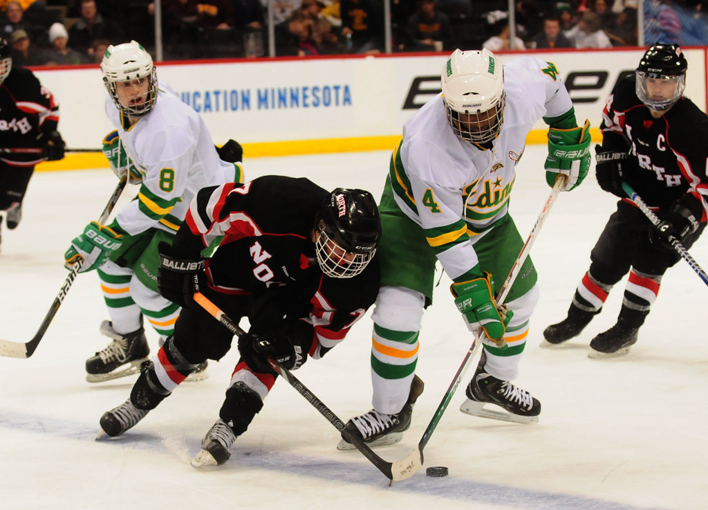 . Lakeville North\'s Nick Poehling, center, and Edina\'s Anthony Walsh, right, fight for the puck in the second period. At left is Edina\'s Cullen Raasch. (Pioneer Press: Scott Takushi)