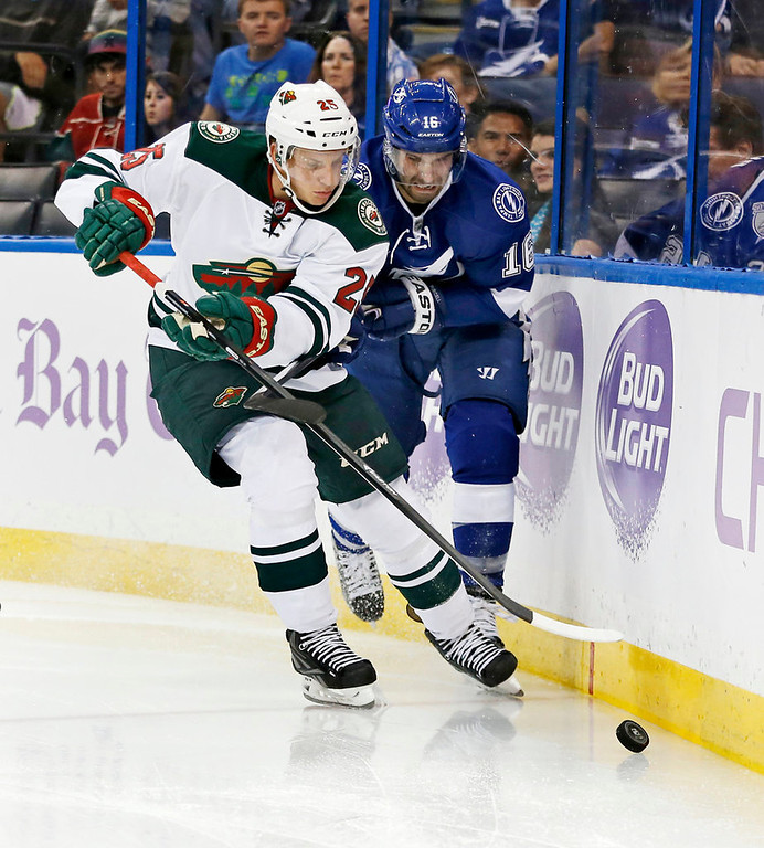 . Jonas Brodin #25 of the Minnesota Wild and Teddy Purcell #16 of the Tampa Bay Lightning battle for a loose puck. (Photo by Mike Carlson/Getty Images)