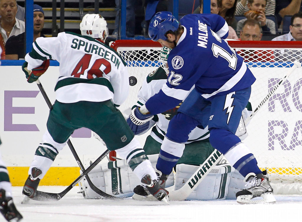 . Jared Spurgeon #46 of the Minnesota Wild and Ryan Malone #12 of the Tampa Bay Lightning look for a rebound in front of goalie Josh Harding #37. (Photo by Mike Carlson/Getty Images)
