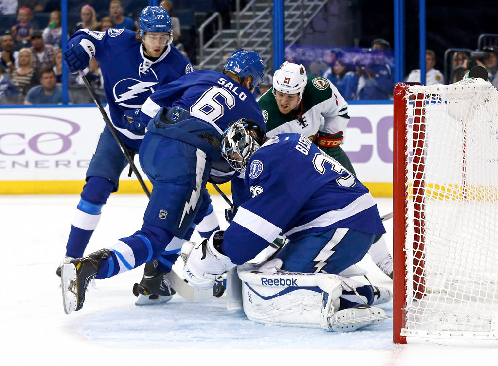 . Goalie Ben Bishop #30 of the Tampa Bay Lightning makes a save on a rebound from Kyle Brodziak #21 of the Minnesota Wild with the help of defensemen Victor Hedman #77 and Sami Salo #6 at the Tampa Bay Times Forum . (Photo by Mike Carlson/Getty Images)