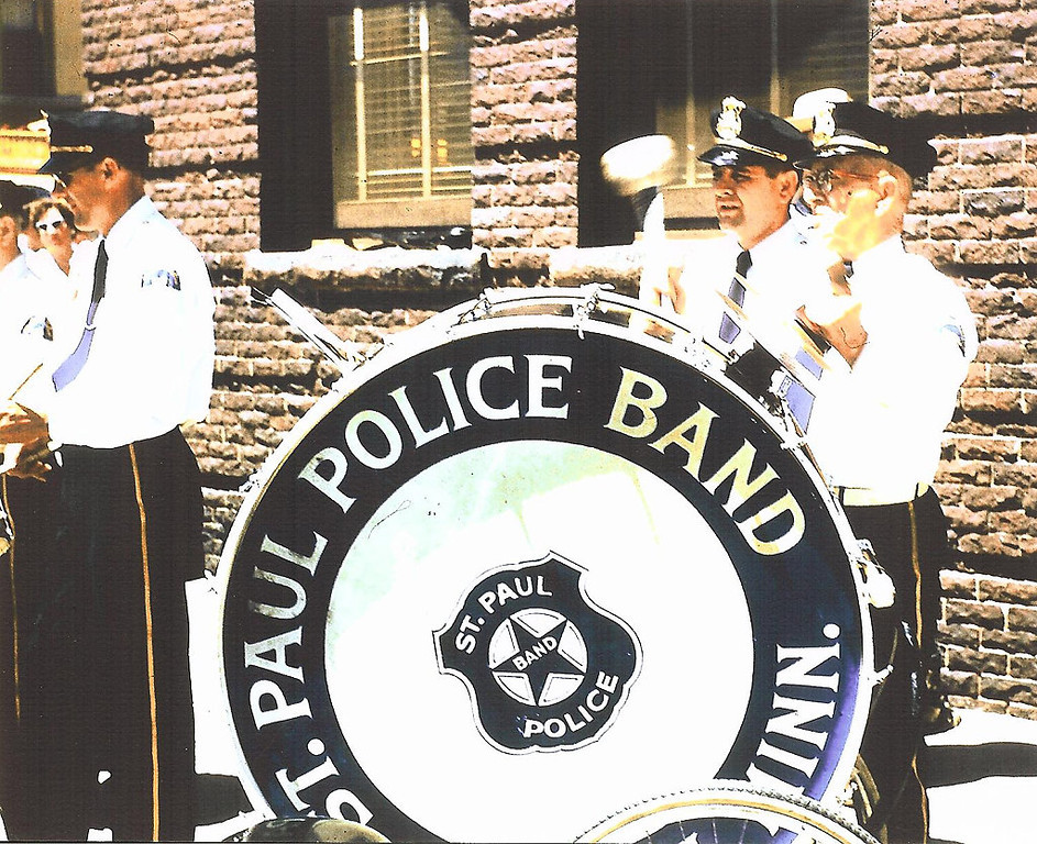 . This photo features from Left to Right:  Officer Ray Rock, Officer Bob Facente, and Bill Francis, who is playing the large bass drum.  The St. Paul Police Band marched in a parade in Rochester, MN in June of 1957 for the Minnesota Peace and Police Officers Association Convention.  The large bass drum was acquired by the police band in the 1930\'s/40\'s and was a feature of the marching band unit through the late 1970ís.  This instrument required two people:  one person to pull the cart that it rested on and a percussionist.  (photo courtesy of Jack Voita)