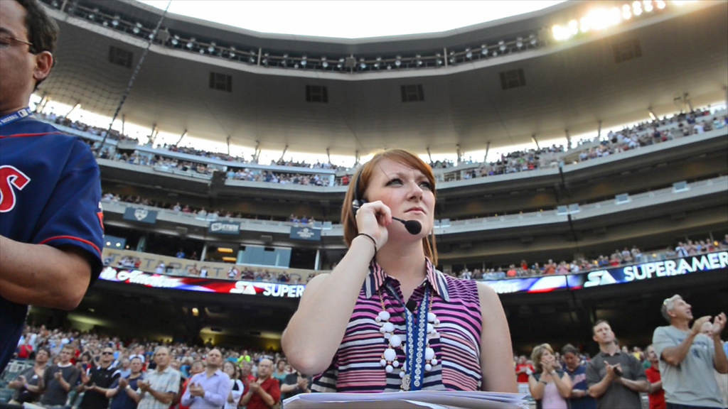 . Twins intern Mary Gillen adjusts her headset as she does the on-field coordinating of pre-game activities and participants. (Pioneer Press: John Autey)