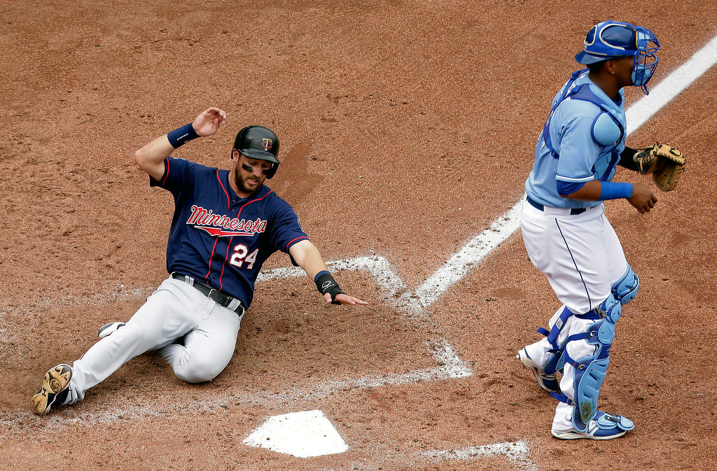 . Minnesota Twins\' Trevor Plouffe (24) slides home past Kansas City Royals catcher Salvador Perez to score on a single hit by Jason Kubel during the seventh inning. (AP Photo/Charlie Riedel)