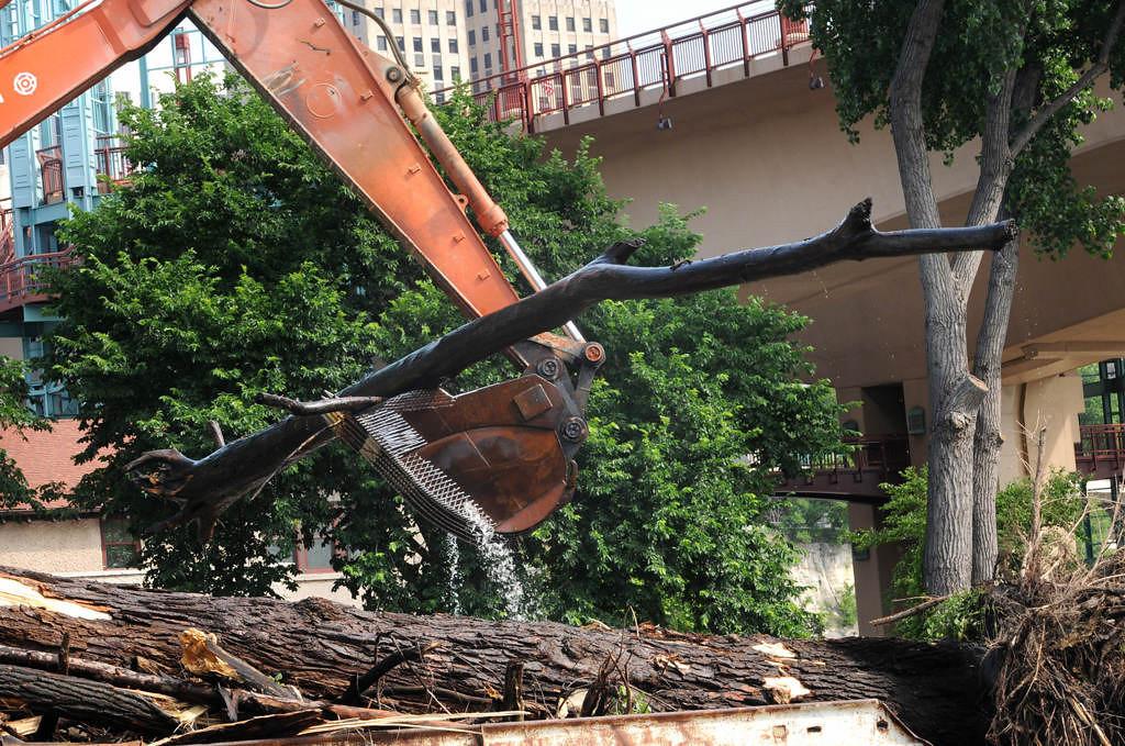 . An excavator scoops up logs and debris from a logjam under the Wabasha Street Bridge.  (Pioneer Press: Jean Pieri)