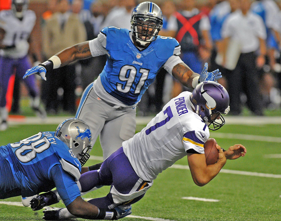 . Vikings quarterback Christian Ponder is brought down by Lions defensive tackle Nick Fairley, left, as defensive end Jason Jones backs up the play in the first quarter.  (Pioneer Press: Chris Polydoroff)
