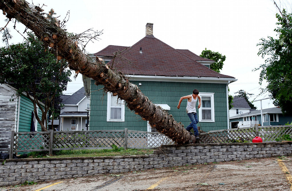 . Zach Hameister hops over a large pine tree that fell near his sister\'s home in Hortonville, Wis. (AP Photo/The Post-Crescent, Sharon Cekada)