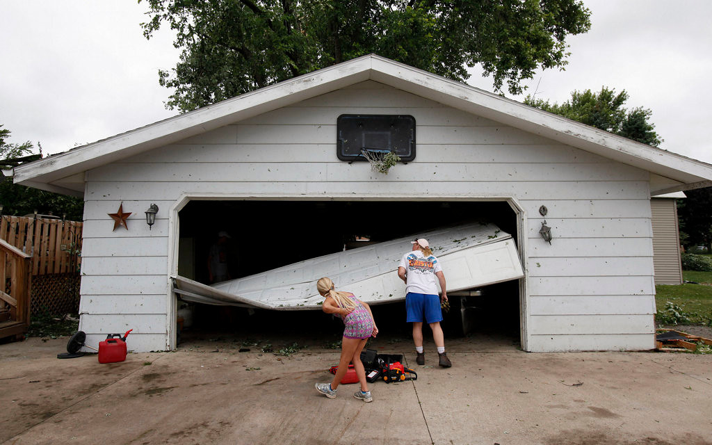 . Lisa Christie and her daughter, Mackenzie, 9, assess the damage to the garage at their home in Hortonville, Wis. (AP Photo/The Post-Crescent, Sharon Cekada)