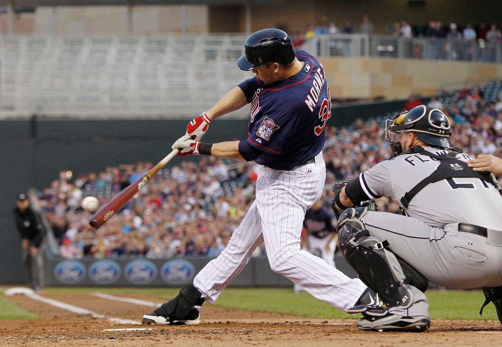 . Minnesota Twins\' Justin Morneau hits a fielder\'s choice RBI against Chicago White Sox starting pitcher Hector Santiago during the third inning of a baseball game, Monday, May 13, 2013, in Minneapolis. (AP Photo/Genevieve Ross)