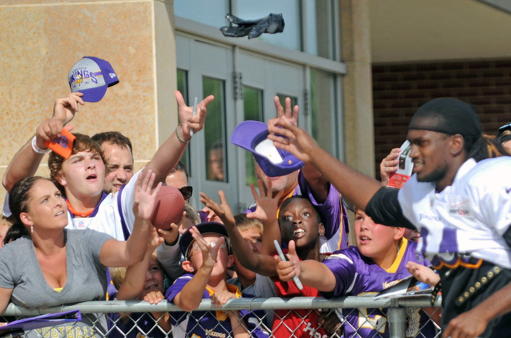 . Fans reach up to try and catch a glove tossed into the crowd by Vikings wide receiver and rookie Cordarrelle Patterson at the conclusion of training camp. (Pioneer Press: Chris Polydoroff)