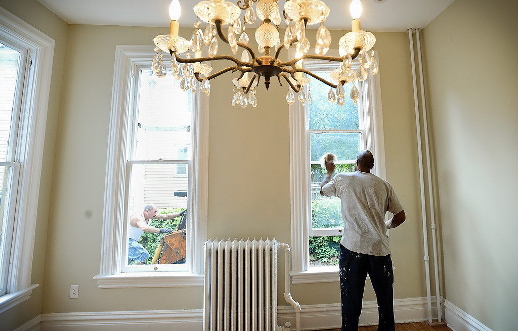 """. Construction worker Darrin Brown cleans windows in a remodeled home at 326 Maria Ave., just down the street from the Wardlaws�. The home, built in 1879, is categorized as \""""pivotal\"""" to the district�s revitalization. (Pioneer Press: Ben Garvin)"""