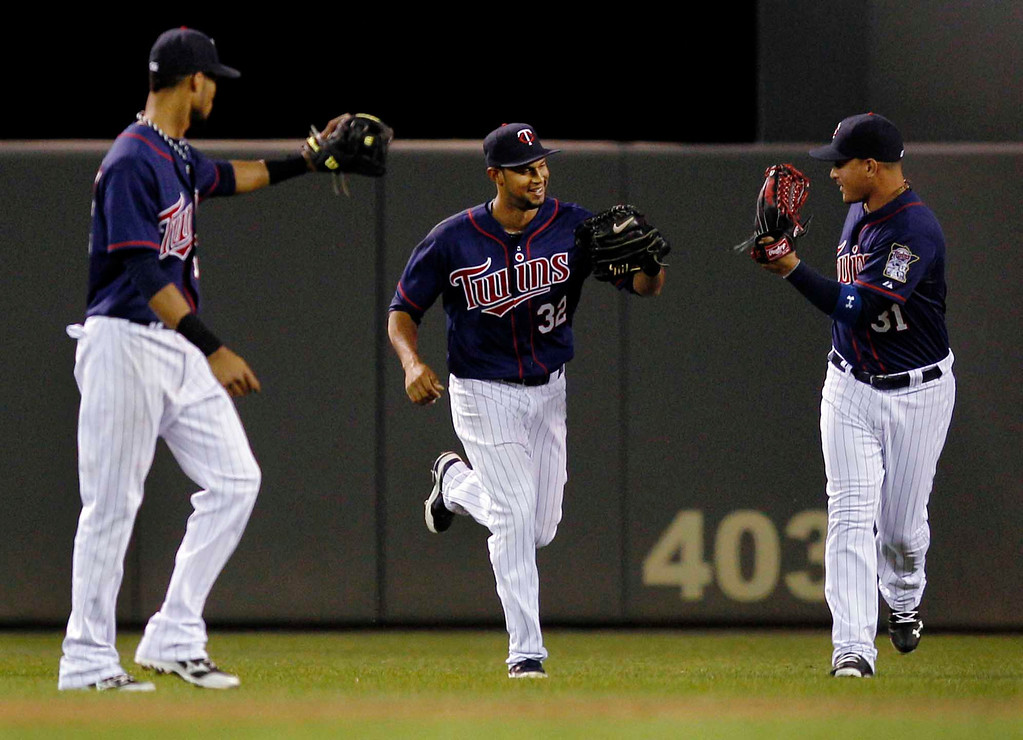. Minnesota Twins center fielder Aaron Hicks (32) is congratulated by teammates Pedro Florimon, left, and Oswaldo Arcia (31) after making a leaping catch for the last out of the sixth inning of a baseball game, Monday, May 13, 2013, in Minneapolis. (AP Photo/Genevieve Ross)